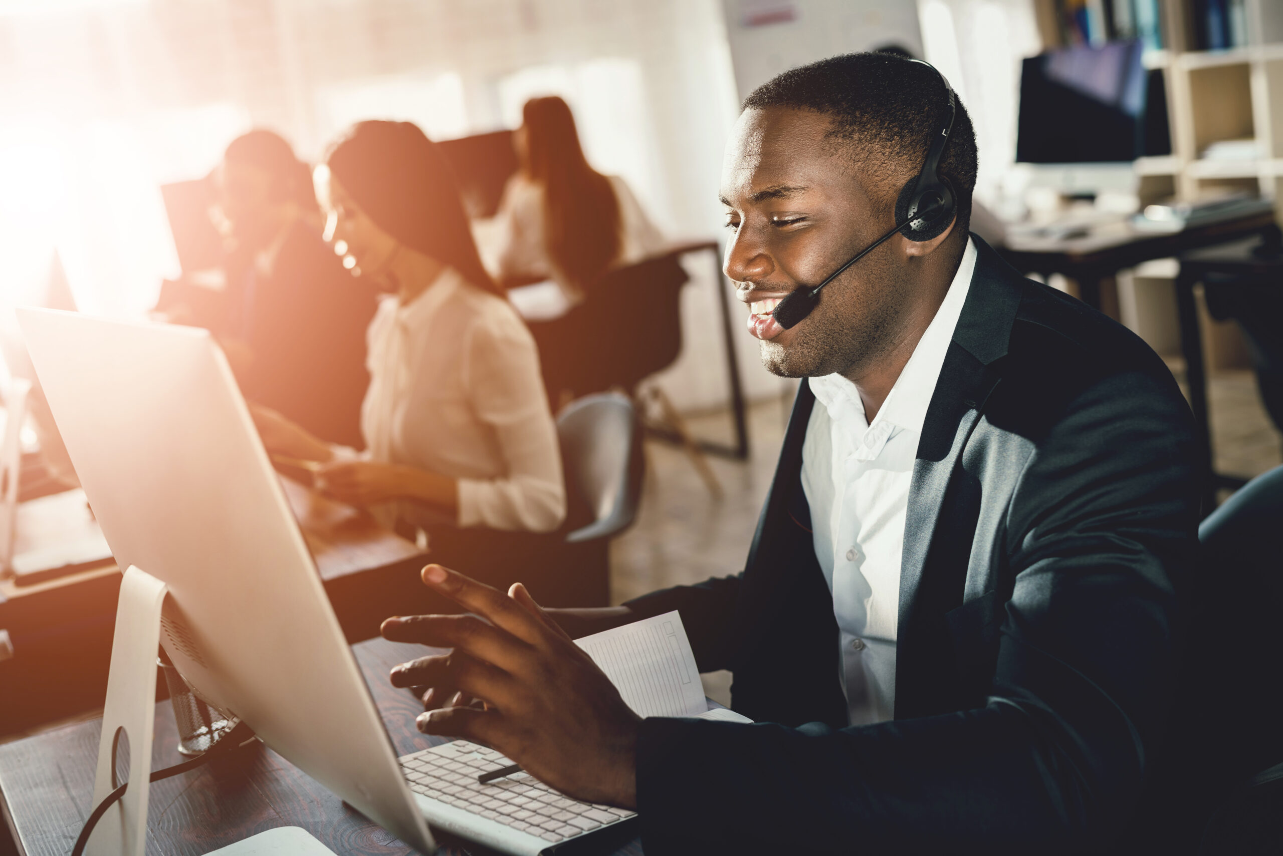 A black guy works in a call center. He has headphones on which they talk with customers. He is an operator and he answers questions.