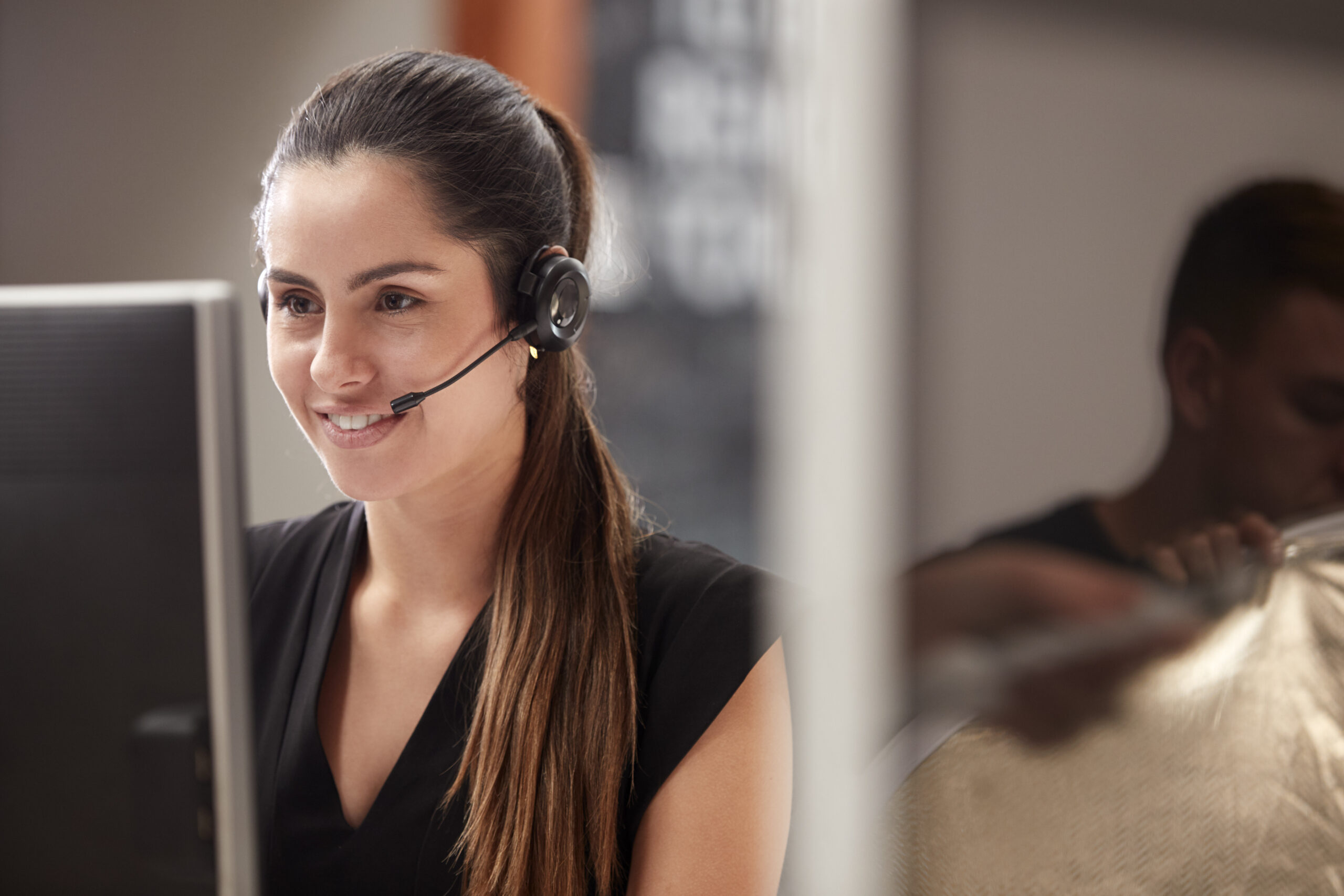 Female Customer Services Agent Working At Desk In Call Center