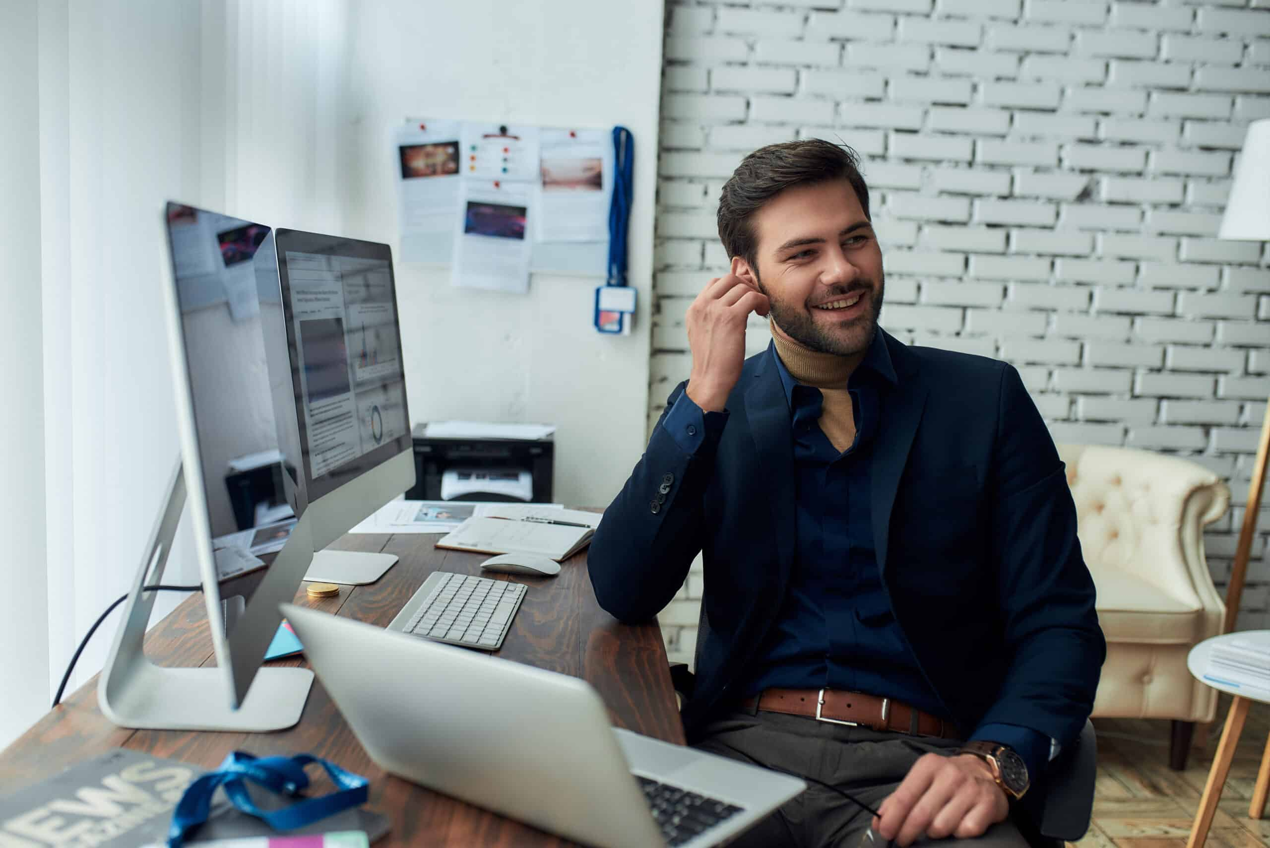 Good talk. Young successful businessman or sales manager wearing wireless earphones, talking with client or partner and smiling, working in the modern office. Focus on man. Business, finance, sales